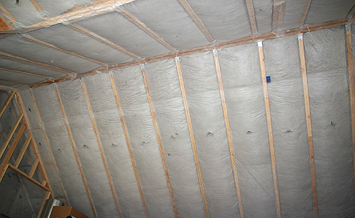 "This is the roof of another house my company is building where 14"" of cellulose insulation has been blown into the roof truss cavities. A tough industrial fabric has been stapled to the trusses to hold the cellulose."