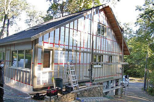 The second layer of foam board insulation has been installed and is fastened to the house by vertical wood firring strips.