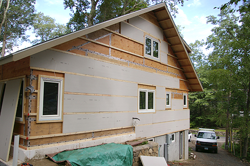 Plywood sheathing joints have been taped, and the first layer of foam board insulation is partially installed.