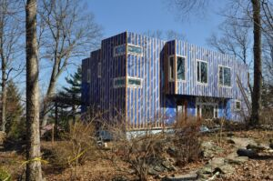 A home under construction, wrapped with a blue weather membrane